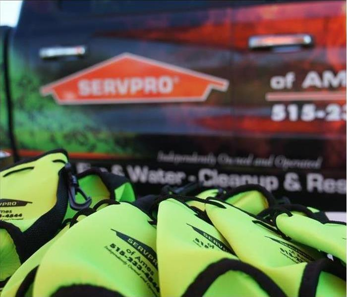 Green SERVPRO Koozies in front of SERVPRO truck