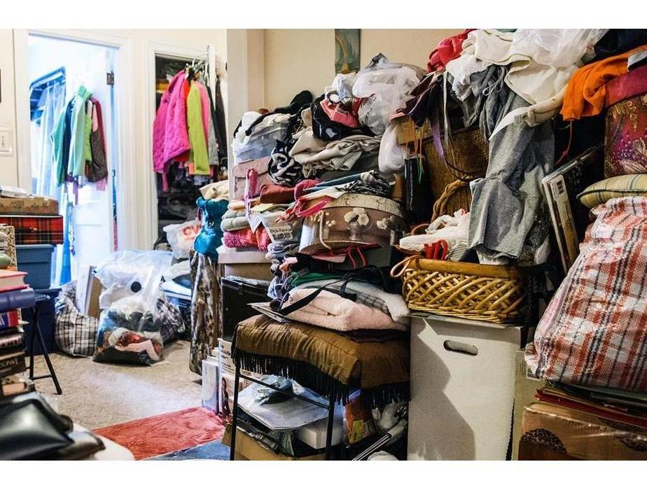 A bedroom cluttered with clothes and other miscellaneous items