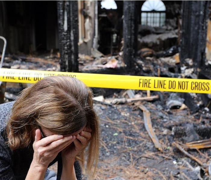 woman with her face in her hands in front of the aftermath of a house fire