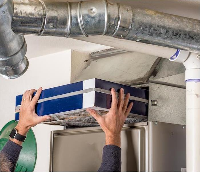 a person in a blue shirt reaching up to change a furnace filter